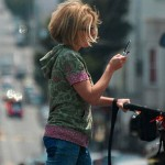 Woman crossing street pushing stroller and viewing smartphone
